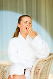 Woman in bathrobe sitting at terrace and yawing Royalty Free Stock Photos