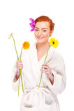 Woman in bathrobe smiling with flowers Stock Photography