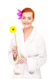 Woman in bathrobe smiling with flowers Stock Images
