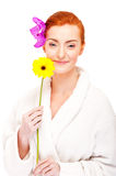 Woman in bathrobe smiling with flowers Stock Image