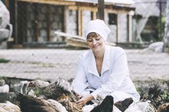 Woman in Bathrobe smiling young veterinarian checks the hens on. A small private farm Stock Photo
