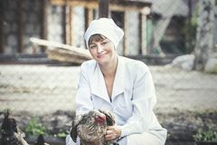 Woman in Bathrobe smiling young veterinarian checks the hens on. A small private farm Royalty Free Stock Photo