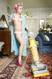 Woman in bathrobe smoking cigarette while cleaning living room with vacuum cleaner Stock Photo