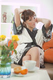 Woman in bathrobe on sofa Stock Images
