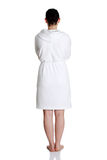 Woman in bathrobe standing back to the camer Stock Photos