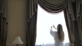Woman in bathrobe stay near the window in hotel room.  stock footage