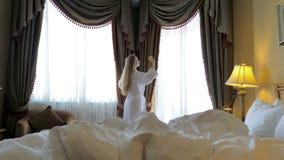 Woman in bathrobe stay near the window in hotel room.  stock video footage