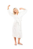 Woman in bathrobe stretching Stock Image