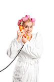Woman in bathrobe talking on telephone Stock Photos