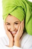 Woman in bathrobe touching face Royalty Free Stock Photo
