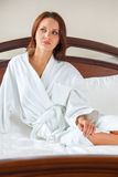 Woman in bathrobe waking up Stock Photo