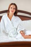 woman in bathrobe waking up Stock Photo