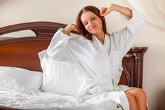 Woman in bathrobe waking up Royalty Free Stock Image