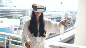 Woman in bathrobe wearing virtual reality headset standing on hotel room balcony and have VR experience stock video