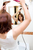 Woman in bathroom. Woman in the mirror drying hair stock images