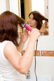 Woman in bathroom. Woman in the mirror drying hair royalty free stock photography