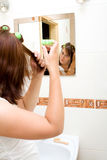 Woman in bathroom. Woman in the mirror drying hair stock image