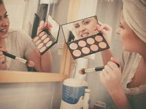 Woman in bathroom applying contour bronzer on brush Royalty Free Stock Image