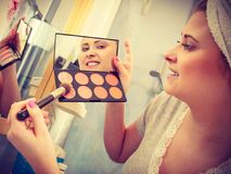 Woman in bathroom applying contour bronzer on brush. Contouring face kit, visage and make up concept. Woman in bathroom applying contour bronzer on brush Stock Images