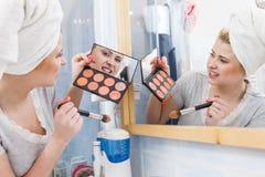 Woman in bathroom applying contour bronzer on brush Stock Image