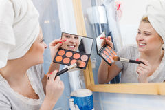 Woman in bathroom applying contour bronzer on brush Stock Photos