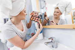 Woman in bathroom applying contour bronzer on brush Stock Images