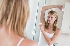 Woman in bathroom applying deodorant Royalty Free Stock Photo