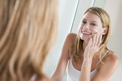 Woman in bathroom applying face cream