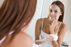 Woman in bathroom applying face cream stock image