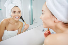 Woman in bathroom applying makeup on Stock Images