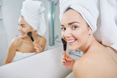 Woman in bathroom applying makeup on Royalty Free Stock Photos