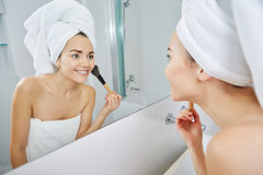 Woman in bathroom applying makeup on Stock Photos