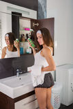 Woman in the bathroom. Beautiful woman choosing beauty products in her bathroom in the morning Stock Image