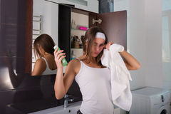 Woman in the bathroom. Beautiful woman choosing beauty products in her bathroom in the morning Royalty Free Stock Photo