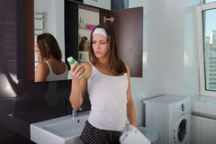 Woman in the bathroom. Beautiful woman choosing beauty products in her bathroom in the morning Stock Images