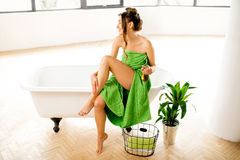 Woman in the bathroom. Beautiful woman in towel taking care about a skin with oil sitting on the bathtub at the bathroom Stock Photos