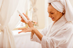 Woman in the bathroom. Beautiful young woman in a bathrobe with a towel on her head applying cream on her hand and smiling while standing in the bathroom Royalty Free Stock Photos