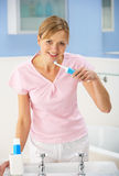 Woman in bathroom brushing her teeth Royalty Free Stock Photos