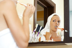 Woman in bathroom brushing teeth Royalty Free Stock Image
