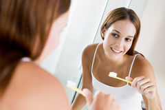 Woman in bathroom brushing teeth Royalty Free Stock Photos