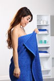 Woman in bathroom checking her body under towel Royalty Free Stock Photography