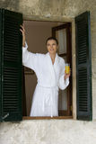 Woman in bathroom drinking orange juice and looking out window Stock Image