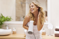Woman in bathroom drying hair Royalty Free Stock Image