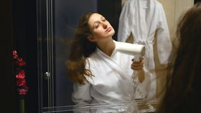 Woman in bathroom drying hair with blow dryer stock footage