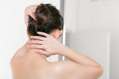 Woman in bathroom looking in to mirror and bundle on her hair. Stock Photo