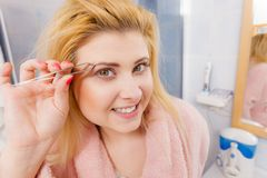 Woman tweezing eyebrows depilating with tweezers. Woman in bathroom plucking eyebrows depilating with tweezers. Girl tweezing removing her facial hairs. Unusual royalty free stock images