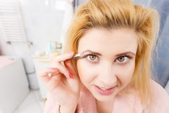 Woman tweezing eyebrows depilating with tweezers. Woman in bathroom plucking eyebrows depilating with tweezers. Girl tweezing removing her facial hairs. Unusual stock photo