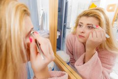 Woman tweezing eyebrows depilating with tweezers. Woman in bathroom plucking eyebrows depilating with tweezers, looking at mirror. Girl tweezing removing her stock photography