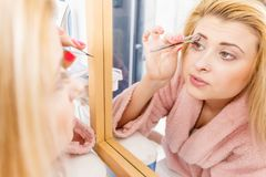 Woman tweezing eyebrows depilating with tweezers. Woman in bathroom plucking eyebrows depilating with tweezers, looking at mirror. Girl tweezing removing her stock images