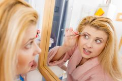 Woman tweezing eyebrows depilating with tweezers. Woman in bathroom plucking eyebrows depilating with tweezers, looking at mirror. Girl tweezing removing her royalty free stock photo